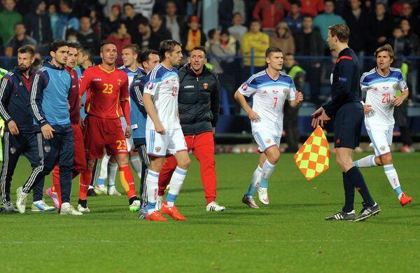 Футболисты сборных Черногории и России покидают поле в сопровождении арбитра
