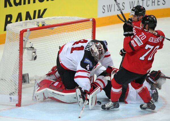 Вратарь сборной Канады Майк Смит (слева) и нападающий сборной Швейцарии Денис Холленштайн (справа)
