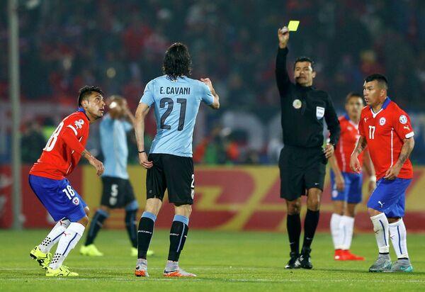 Главный арбитр матча Кубка Америки между сборными Чили и Уругвая Сандро Риччи (в центре) показывает желтую карточку форворду уругвайцев Эдинсону Кавани (слева)