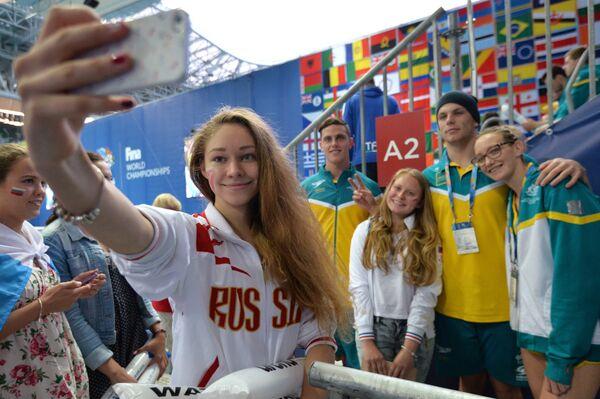Болельщицы фотографируются со спортсменами сборной Австралии во время соревнований по плаванию на XVI чемпионате мира по водным видам спорта в Казани