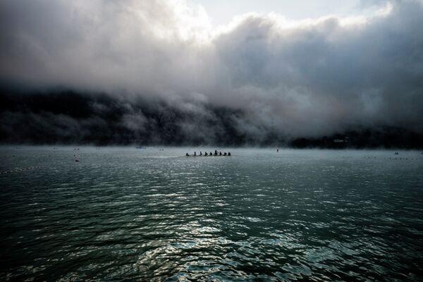 Гребцы плывут в тумане на озере Эгебелет (Франция) в преддверии старта чемпионата мира по академический гребле