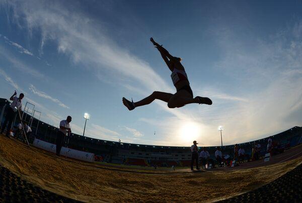 Спортсменка во время соревнований по прыжкам в длину