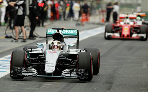 Пилот Мерседеса Льюис Хэмилтон (на переднем плане) и гонщик Феррари Себастьян Феттель во время квалификации Гран-при Австралии