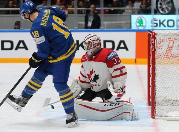 Форвард сборной Швеции Микаэль Баклунд и вратарь сборной Канады Кэм Тальбо (справа)