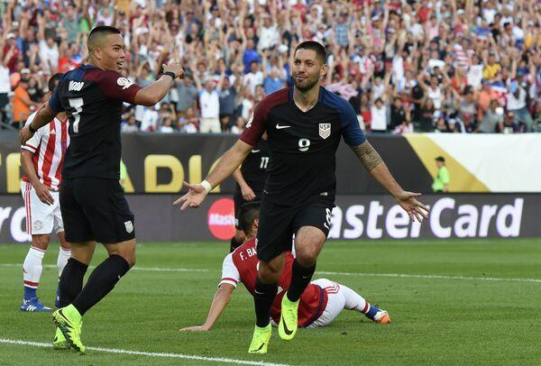 Полузащитник сборной США по футболу Клинт Демпси (справа) празднует забитый гол