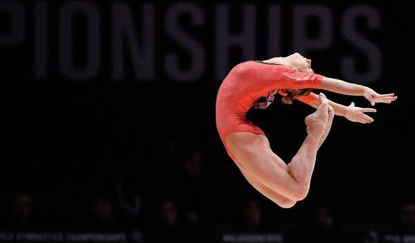 Виктория Комова выполняет упражнения на бревне