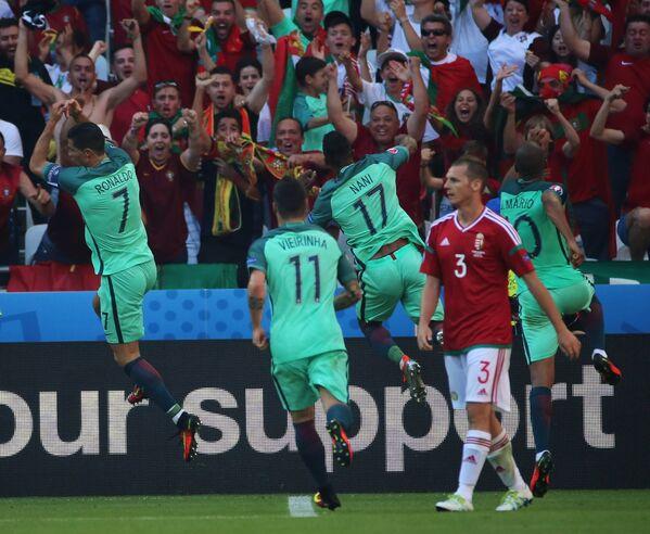 Футболисты сборной Португалии Криштиану Роналду, Виейринья, Нани и Жоау Мариу (слева направо на втором плане) радуются забитому голу
